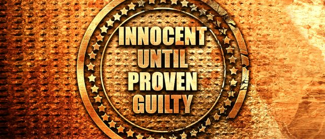 "embossed emblem saying ""Innocent Until Proven Guilty"""