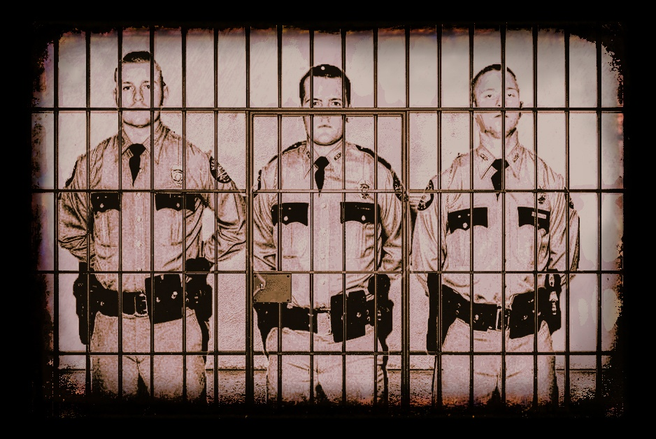 uniformed cops in a jail cell