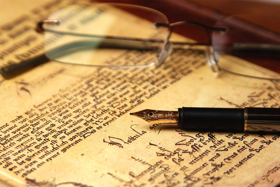 parchment, glasses, fountain pen signify writing criminal defense blog posts