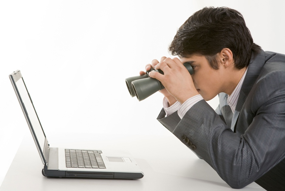 man tries to investigate computer with binoculars