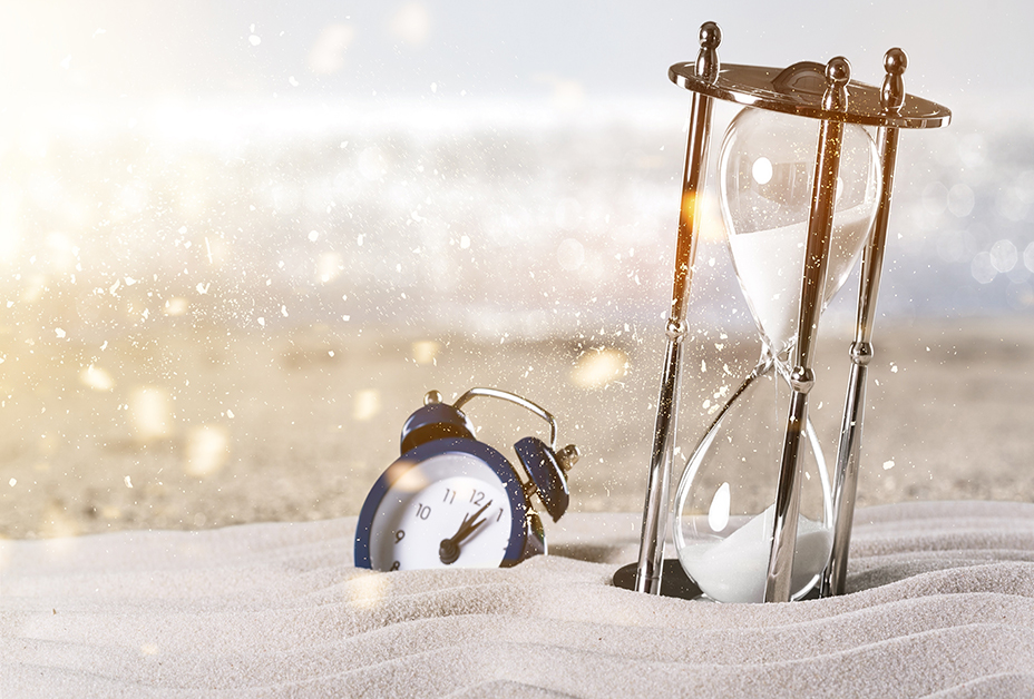 time flies signified by clock and hourglass in the sand of the beach