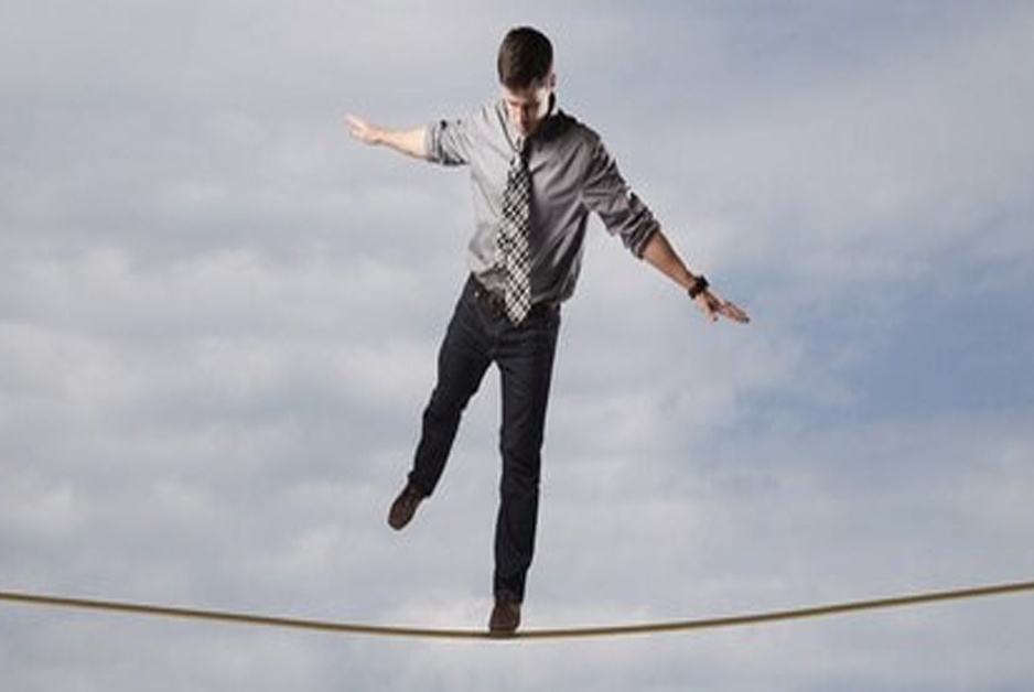 Businessman performing high wire empathic act - walking on wire in business attire