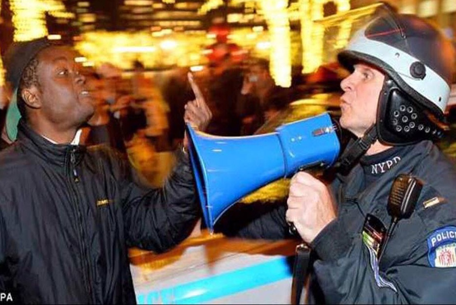 Protester flips off police officer in this photo