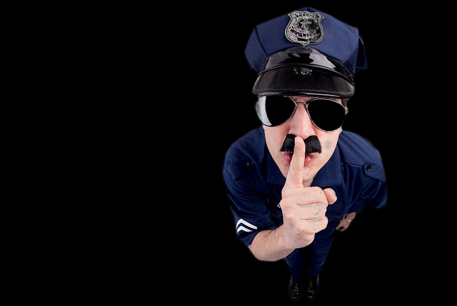 Police officer making shush sign with finger in front of mouth