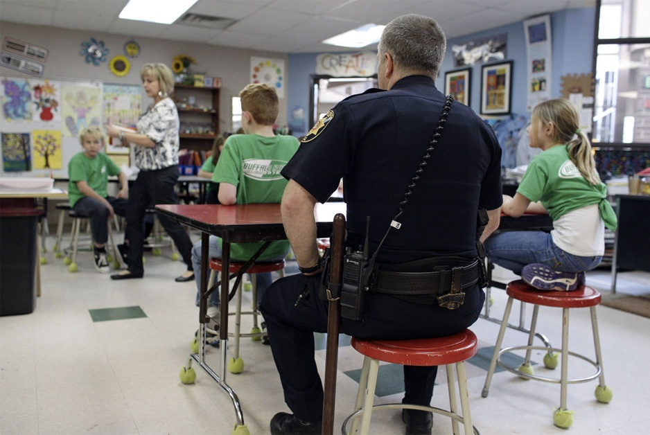 police officer in classroom guarding children signifies our commitment to save just one child